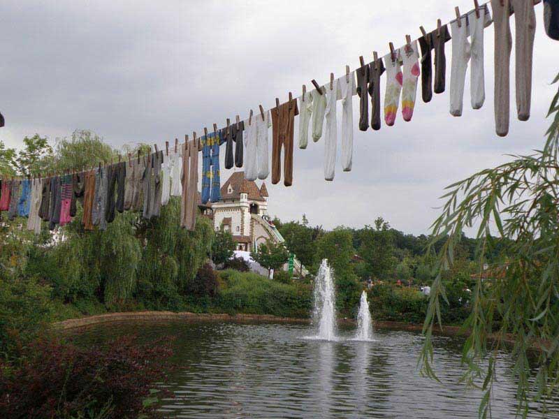 חבלי הכביסה עמוסי הגרביים וברקע מגלשת האמבטיה הגבוהה