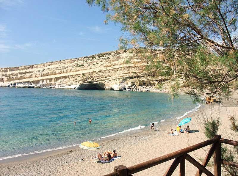 חוף מָטאלָה והמערות העתיקות ברקע