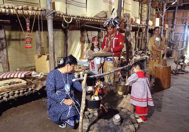 שחקנים בתלבושות אינדיאניות מסורתיות באתר המדינה ההיסטורי גאנוֹנדאגאן