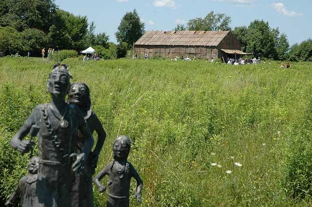 פסלים של דמויות אינדיאניות על רקע העתק של בית עץ מסורתי באתר